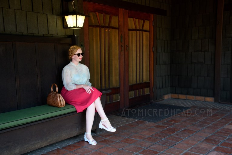 Sitting on the back porch of the Gamble House, wearing a pale blue sheer blouse and magenta skirt with white trim, and a brown woven basket purse.