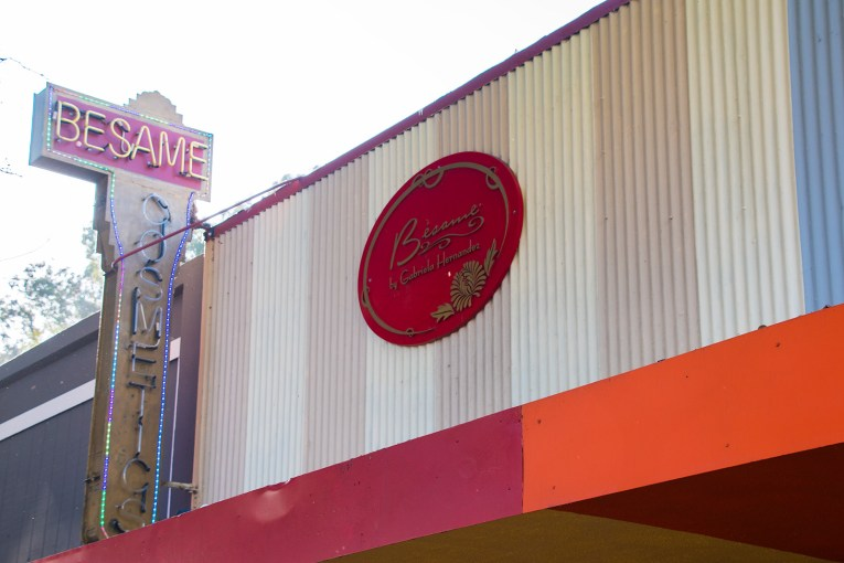 """Sign for Besame Cosmetics. A bright red oval, reading """"Besame Cosmetics"""" accompanied by neon reading the same."""