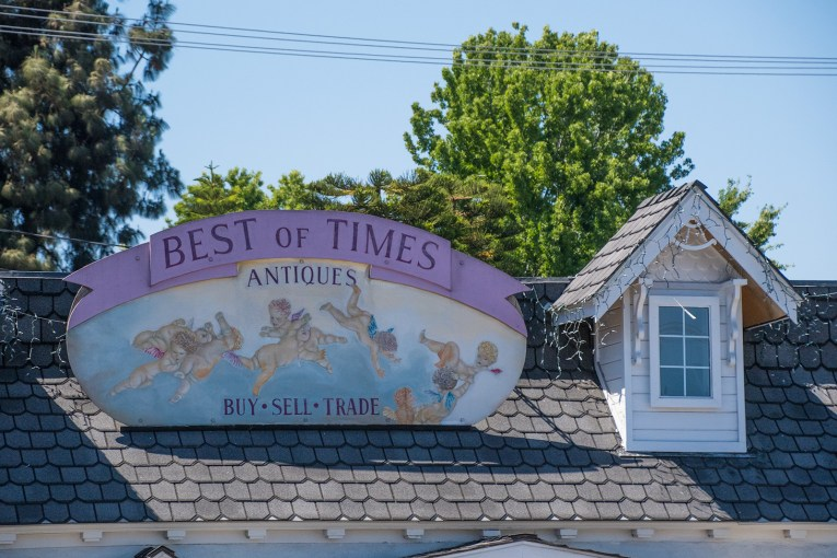 Sign for Best of Times Antiques, painted with several cherubs, flying around clouds.