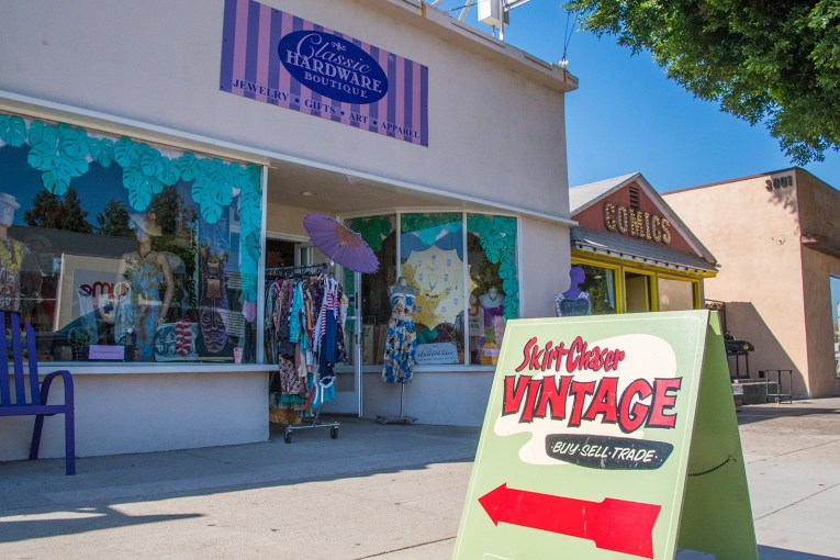 "Storefront of Classic Hardware, with vintage clothing inside the windows. An A-frame board outside reads ""Skirt Chaser Vintage"" advertising for the vintage within as well."