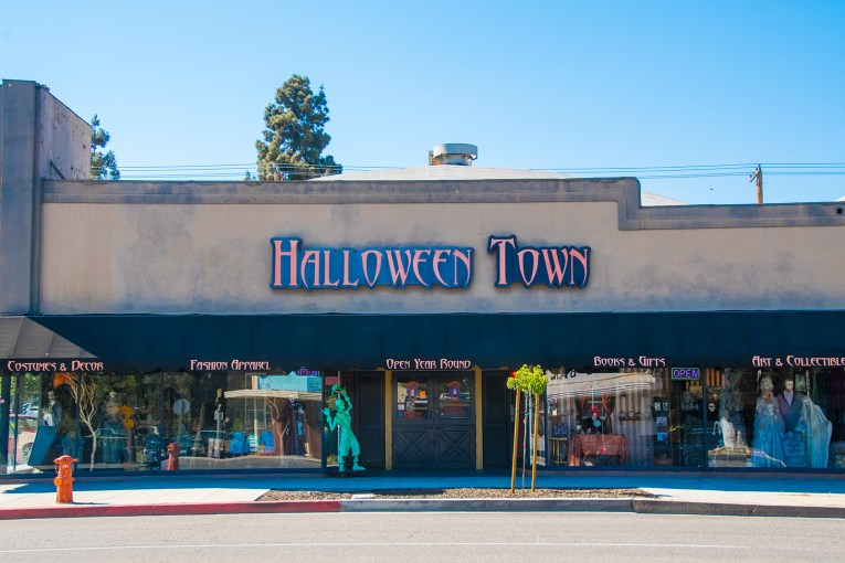 """Storefront for Halloween Town. Large creepy text reads """"Halloween Town"""" in orange and black letters, windows are filled with tombstones, vampires, goblins, and fortune tellers."""