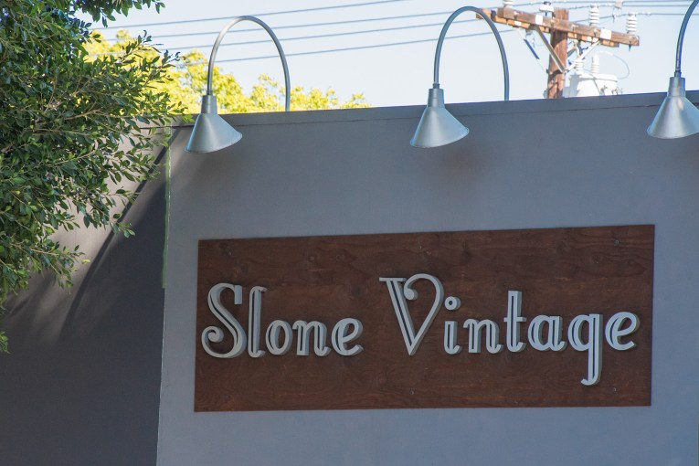 Sign for Slone Vintage, silver letters over a large dark wood sign.