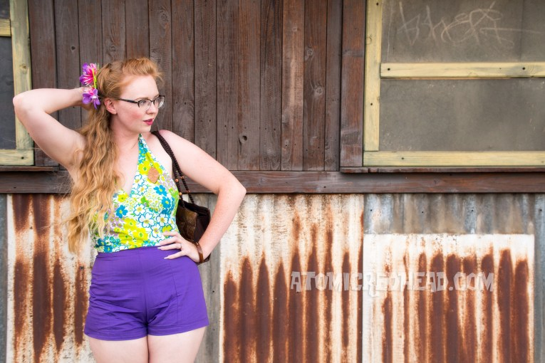 Me enjoying the fun atmosphere of the drive-in, wearing a purple, blue, and green floral halter top, purple shorts, and wood tiki brooch.