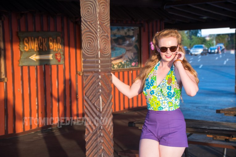 "Me enjoying the fun atmosphere of the drive-in, wearing a purple, blue, and green floral halter top, purple shorts, and wood tiki brooch. Behind a carved wood sign reads ""Snack Bar"" and paintings of Hawaiian beaches hang on either side."