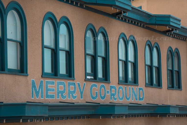 "Side of the Hippodrome, a tan building, with navy blue trim, and painted on the side ""Merry-Go-Round"""