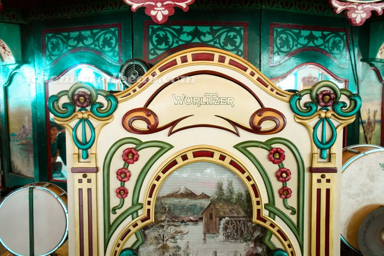 The Wurlitzer for the carousel, painted in many different colors, and a scene of a cabin with a water wheel on the speaker.