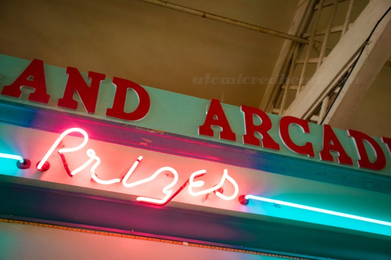 "Inside Playland, pink neon reading ""Prizes"""