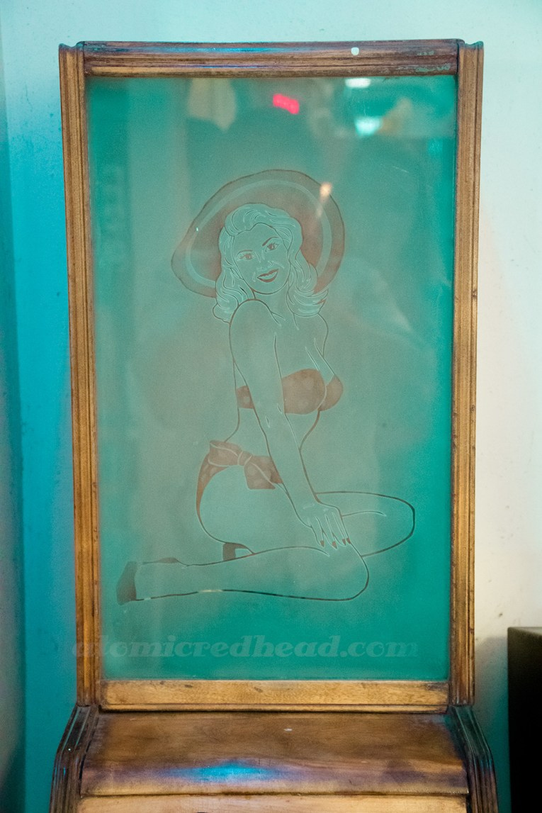 Inside Playland - a 1950s etched glass of a pin-up in a bikini and large sunhat to advertise what was likely a cheesecake show to watch.