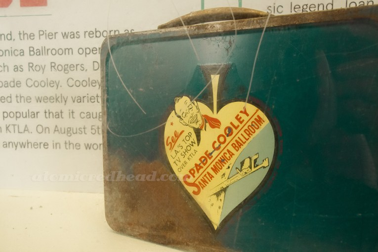 A vintage lunchbox featuring a cartoon of Spade Cooley, along with an illustration of the pier.