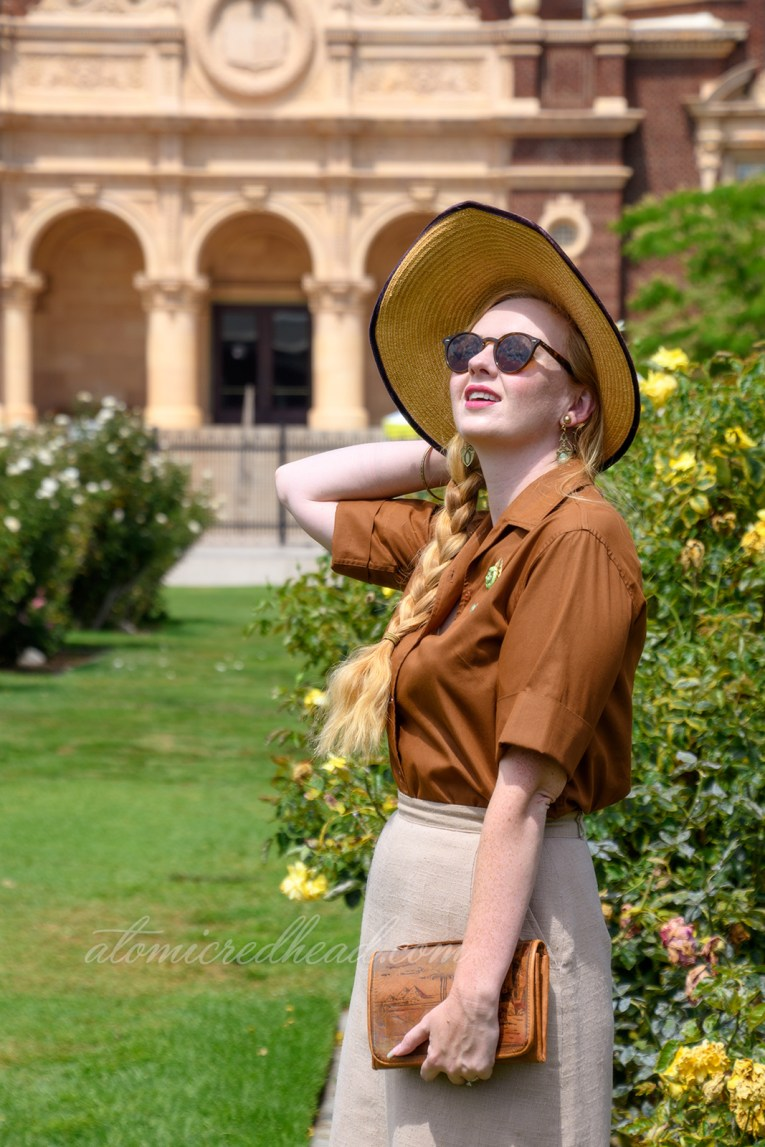 Me, outside of the museum in the rose garden, wearing a straw hat in brown velvet trim, a brown blouse with a gold and green brooch featuring the face of King Tut, a tan linen skirt, and brown and tan shoes.