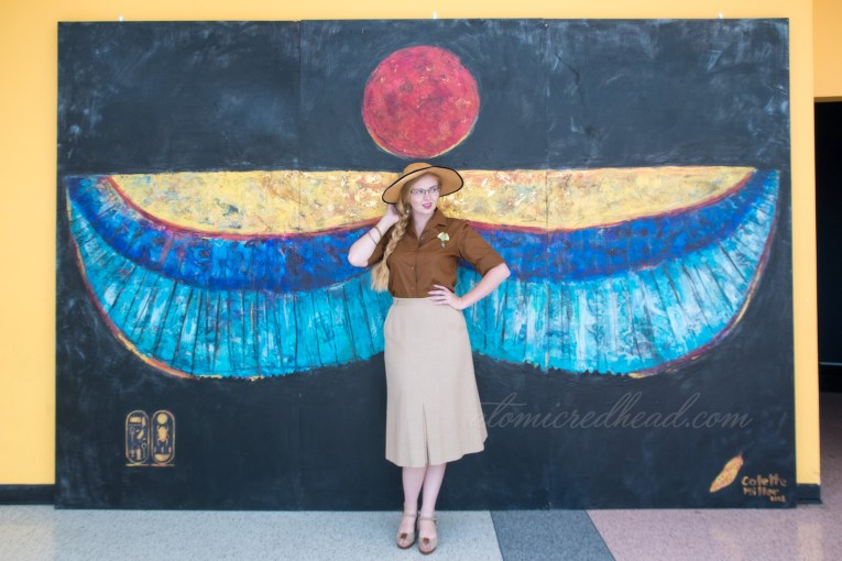 A mural featuring Egyptian style wings with the sun above.