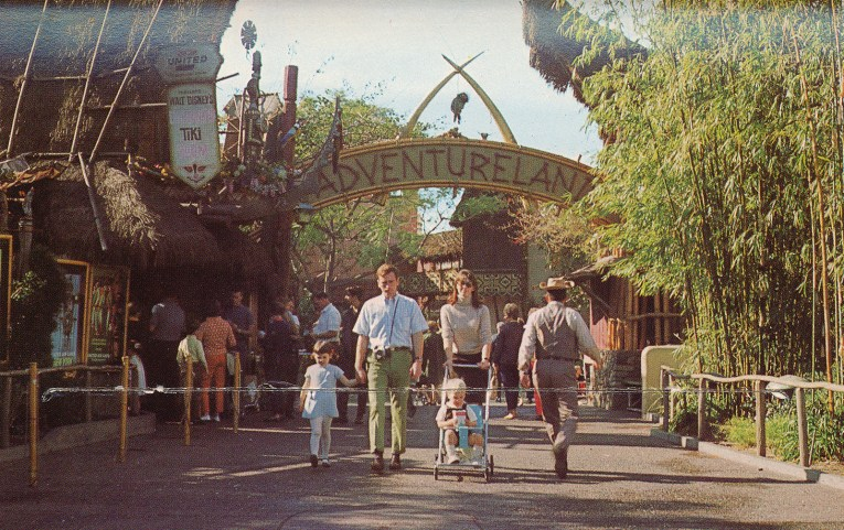 """The entrance to Adventureland, a combination of tiki and African culture merge together. Crossed elephant tusks stand above the text reading """"Adventureland"""" that is spelled out in wood. The Enchanted Tiki Room off to the left."""