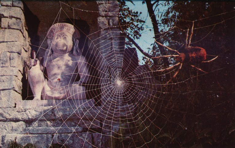 A massive spiderweb with a spider perched in it takes over a statue of a sitting monkey holding a crystal.