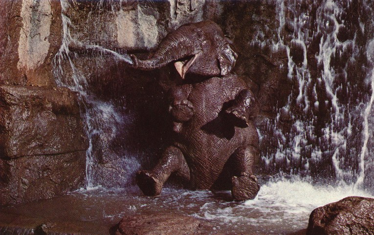 An elephant sits in a waterfall, blowing water from her trunk.