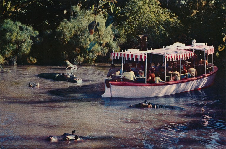 A Jungle Cruise boat glides through a hippo pool with hippos peeking out from the water.
