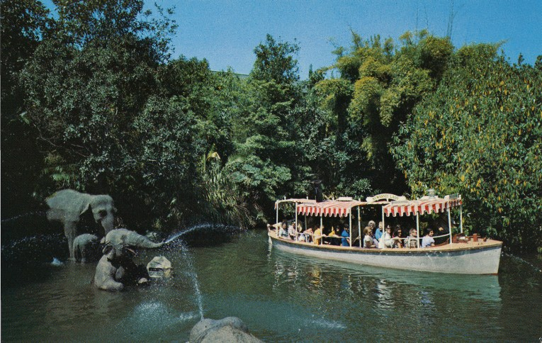 A Jungle Cruise boat glides through the sacred elephant bathing pool with a variety of elephants.