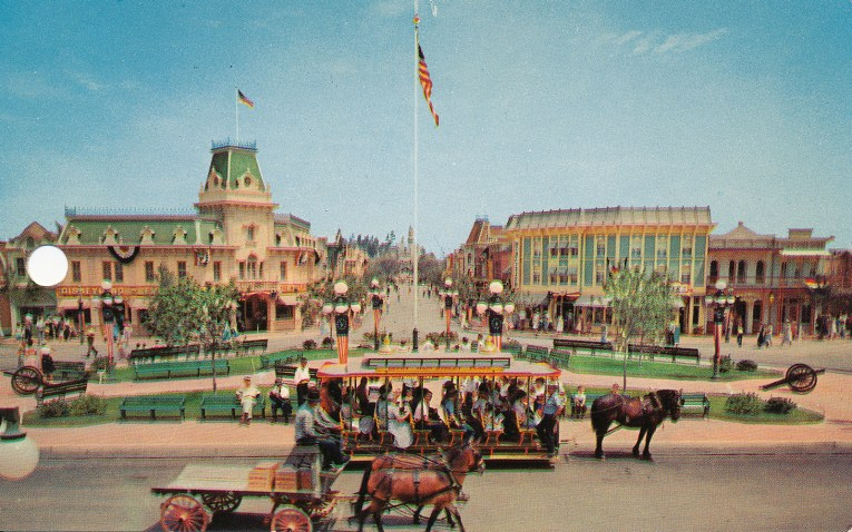 A look down Main Street, with colorful buildings reflecting the late 1890s and early 100s, fanciful Victorian buildings, a horse-drawn streetcar boards Guests.