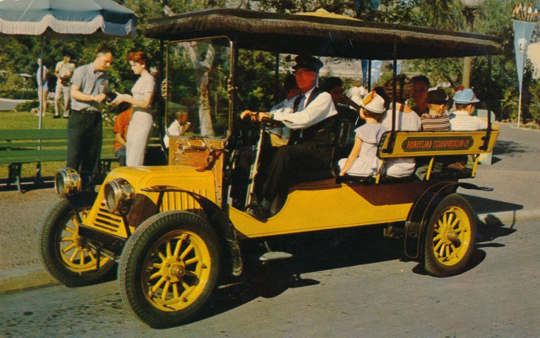 A yellow horseless carriage for Guests to ride in up and down Main Street.