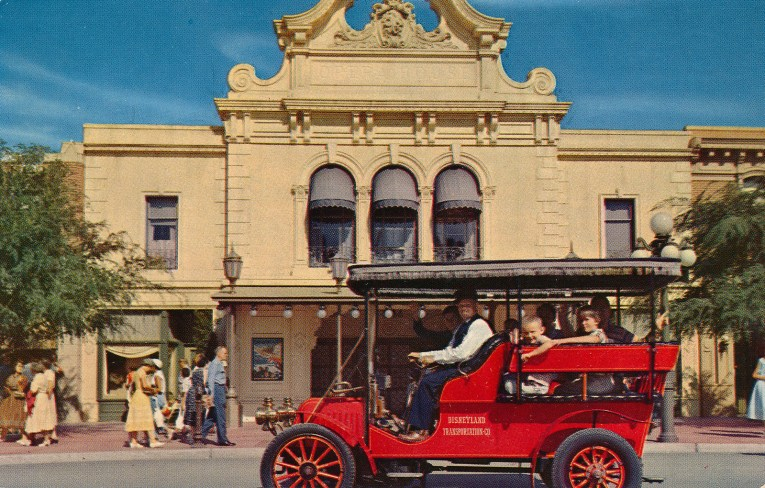 A red horseless carriage in front of the Opera House.