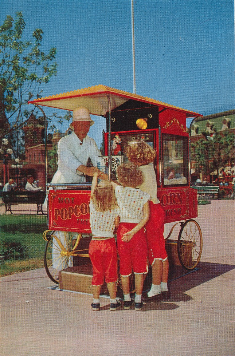 A vendor along Main Street sells popcorn to a trio of little girls all dressed alike.
