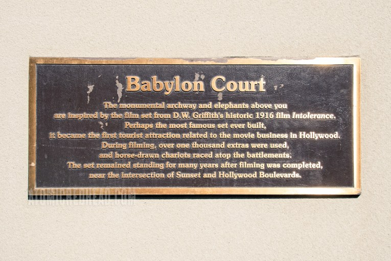 """A plaque reads: """"Babylon Court. The Monumental archway and elephants above you are inspired by the film set from D.W. Griffith's historic 1916 film Intolerance. Perhaps the most famous set ever built, it became the first tourist attraction related to the movie business in Hollywood. During filming, over one thousand extras were used, and horse-drawn chariots raced atop the battlements. The set remained standing for many years after filming was completed, ear the intersection of Sunset and Hollywood Boulevards."""