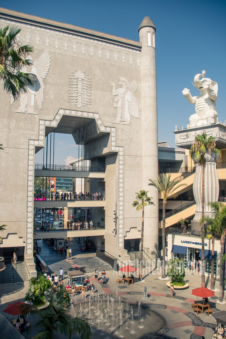 To the left, the Babylonian arch/bridge, over six stories in height. A white elephant sits atop a pillar to the right, also towering over five stories tall.