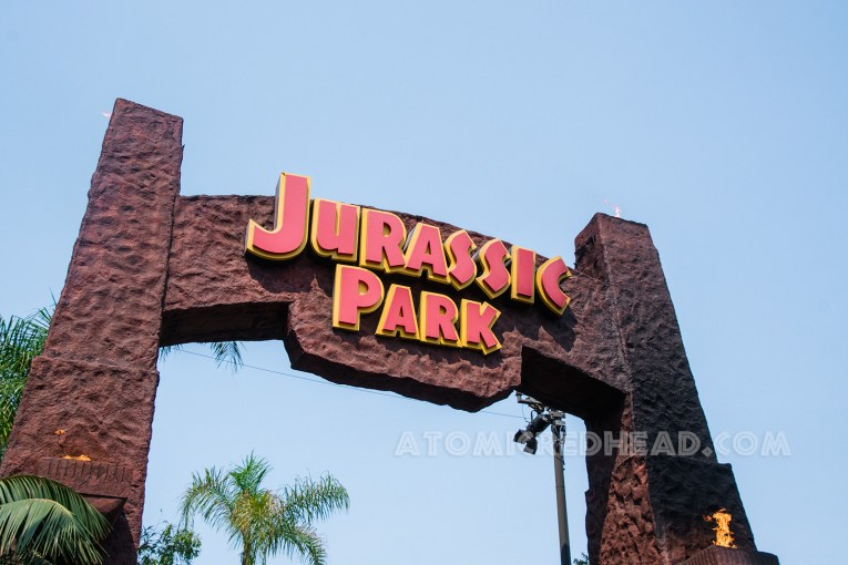 """The archway into the Jurassic Park ride, just like in the film - a medium brown stucco like material with red text outlined in yellow reading """"Jurassic Park"""""""