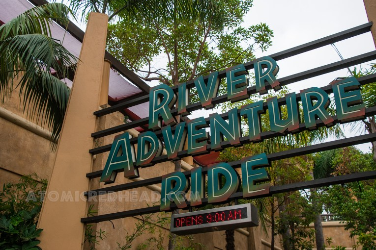 "After passing through the archway you pass under the sign reading ""River Adventure Ride"" in green text."
