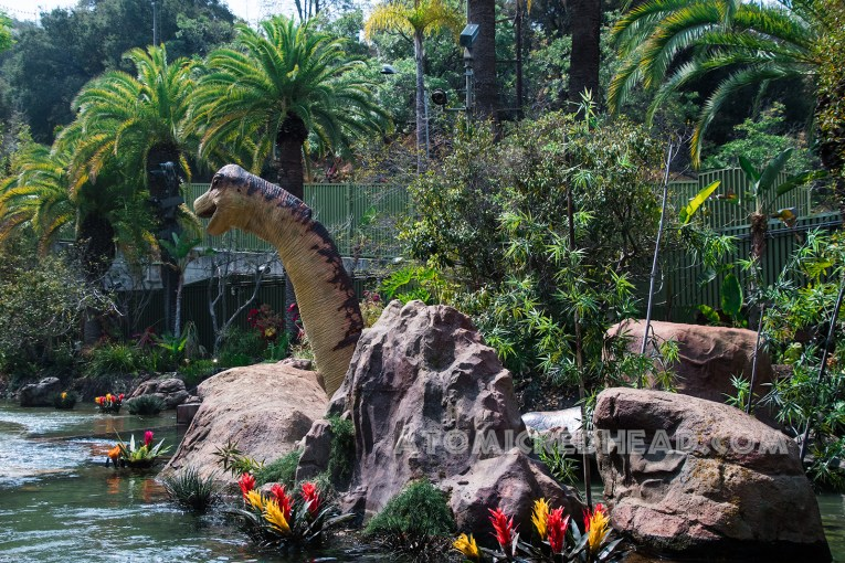 A dinosaur lounges in a pool and rocks and flowers spring up.