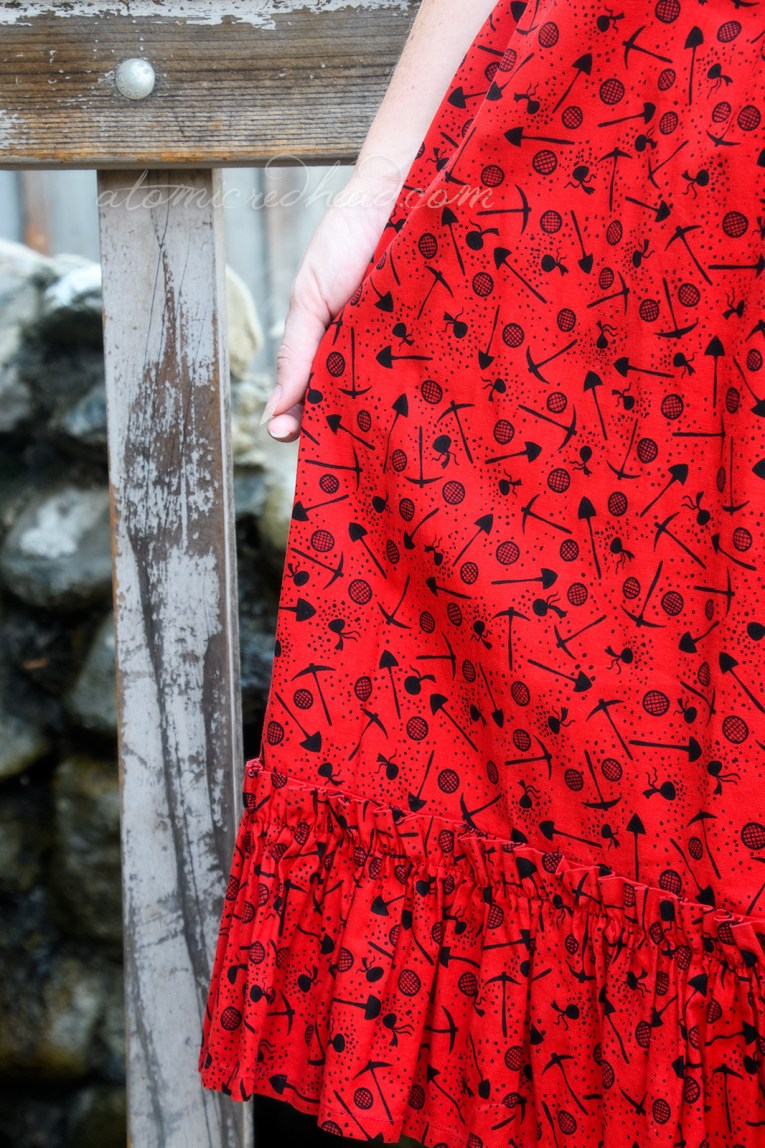 Close-up of my skirt, red with a print of black pick axes, shovels, sluice pans, and bags of gold.
