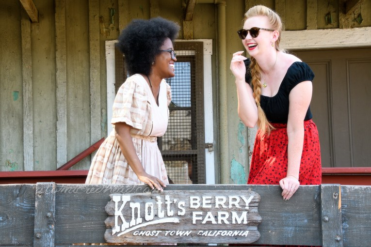 """Carla and I in an old wagon that reads """"Knott's Berry Farm Ghost Town California"""" on it."""