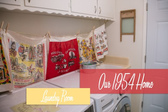 Our 1954 Home: Laundry Room text over a look at the vintage aprons that hang above the washer and dryer. A vintage washboard hangs above the sink in the back.