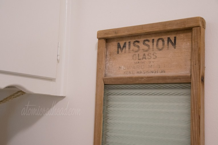 """A close up of the vintage washboard, made of wood and glass, reads """"Mission Glass"""" across the top in black letters."""