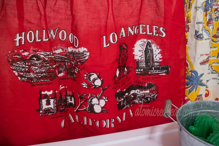 "Close-up of the red apron. Across the top it reads ""Hollywood Los Angeles"" and across the bottom ""California."" The illustrations include the Hollywood Bowl, Farmer's Market, Grauman's Theater, Sad Eye Joe of Knott's Berry Farm, Los Angeles City Hall, and Olvera Street."