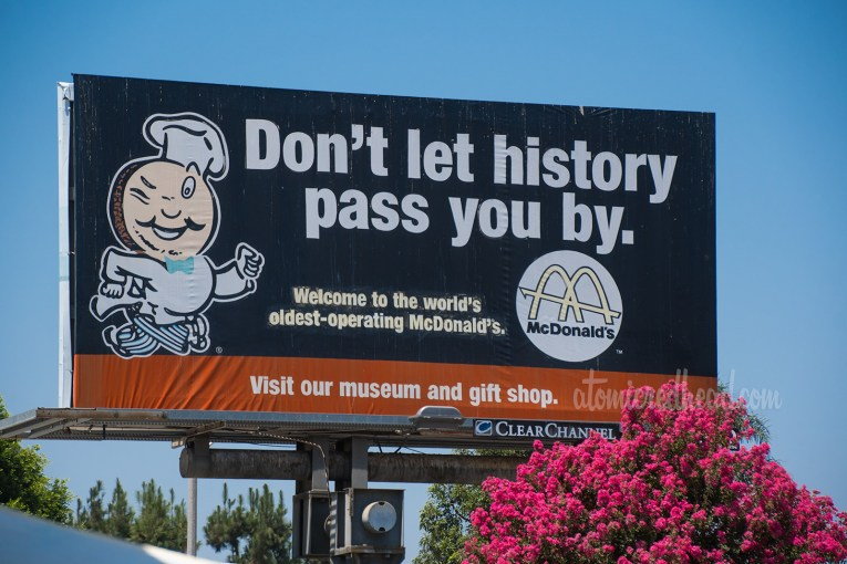 """Billboard for the McDonald's, featuring Speedee and the text """"Don't let history pass you buy."""""""