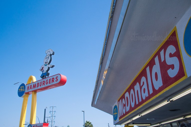 """A part of the building, reading """"McDonald's"""" and the tall Speedee sign in the background."""