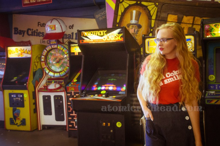 """Inside the Redondo Fun Factory - wearing a vintage red shirt reading """"Have a Coke and a smile"""" and wide leg blue jeans. In the background a variety of 80s arcade games, behind them a ton of vintage signs."""