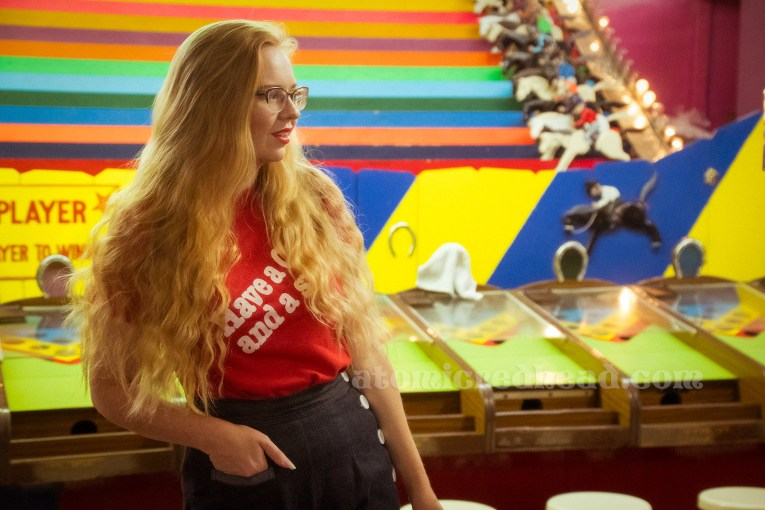 "Inside the Redondo Fun Factory - wearing a vintage red shirt reading ""Have a Coke and a smile"" and wide leg blue jeans. In the background the multi-color horse trot game."