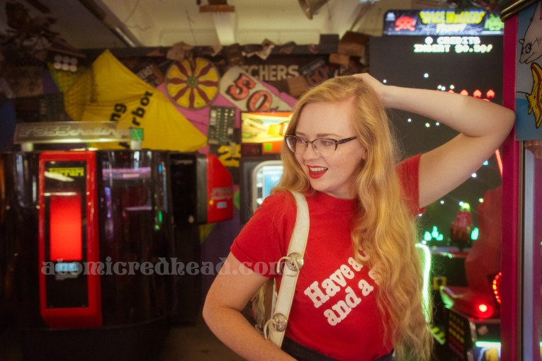 """Inside the Redondo Fun Factory - wearing a vintage red shirt reading """"Have a Coke and a smile"""" and wide leg blue jeans. In the background a variety of arcade games and bizarre signs hang on the wall and from above."""