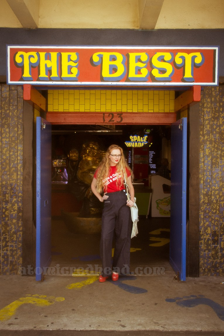 "Standing in the doorway of the Fun Factory under a giant red and yellow sign reading ""THE BEST"""
