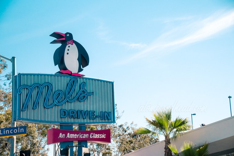 "A dapper penguin sits atop a blue neon sign reading ""Mel's Drive-In An American Classic"""