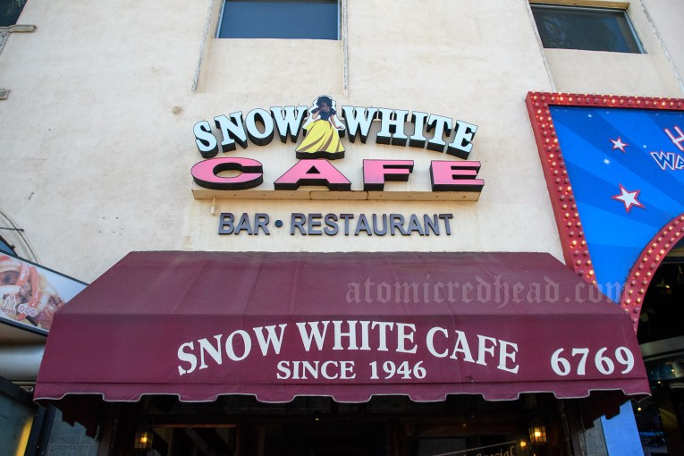 "Sign outside of the Snow White Cafe. Reads ""Snow White Cafe Bar Restaurant"" and features an image of Snow White in a yellow skirt and blue top. A maroon awning reads ""Snow White Cafe Since 1946."""