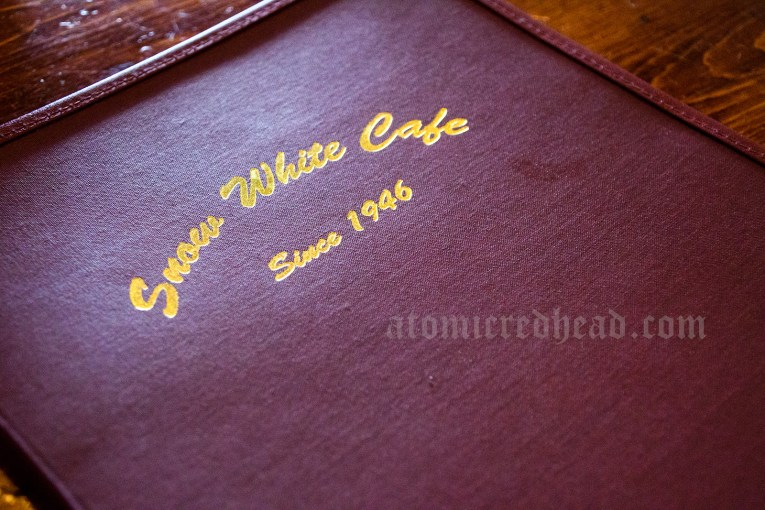 "Cover of the menu at the Snow White Cafe, maroon vinyl in gold script reads ""Snow White Cafe Since 1946"""