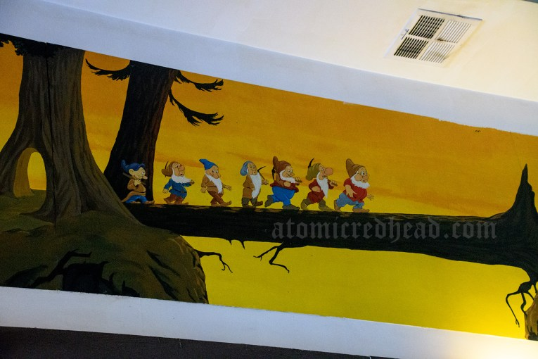 A mural of the seven dwarves marching along a fallen tree.