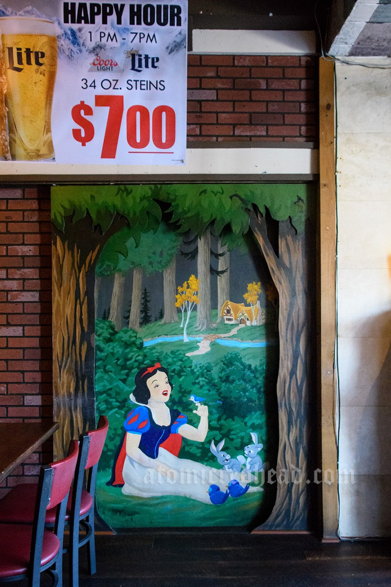 A mural of Snow White seated with various forest creatures, a bird rests on her hand.