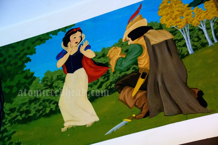 Mural of Snow White and the Huntsman, who is on his knee, telling him how he cannot kill her. A knife rests by his foot.