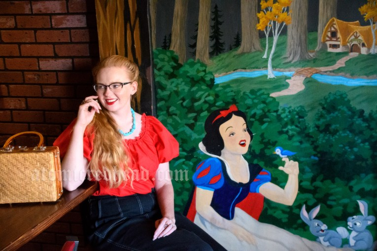 Myself, wearing a red peasant top, black capri jeans, and white moccasins, seated near the mural of Snow White seated in the forest.
