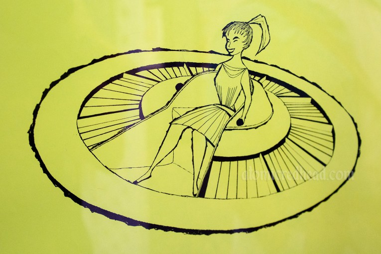 Close-up from the Flying Saucers attraction poster, features a girl in a UFO like ride vehicle.