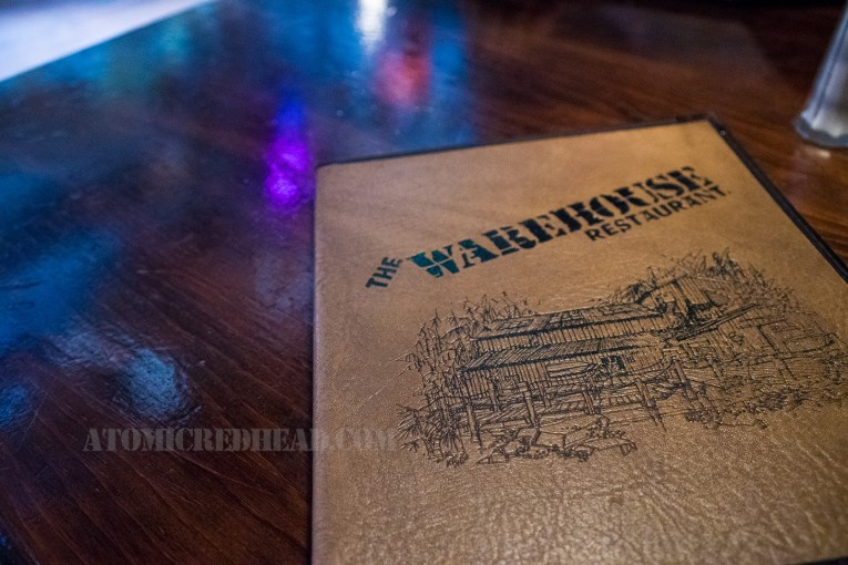 "The menu for The Warehouse, a tan faux leather, embossed with black, text reading ""The Warehouse"" and an illustration of the front of the building."