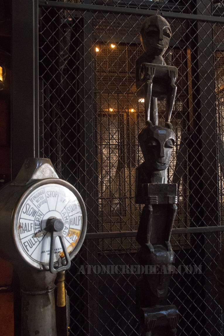 Inside: A ship's engine order telegraph stands next to a tall black tiki totem, in front of a cage elevator.